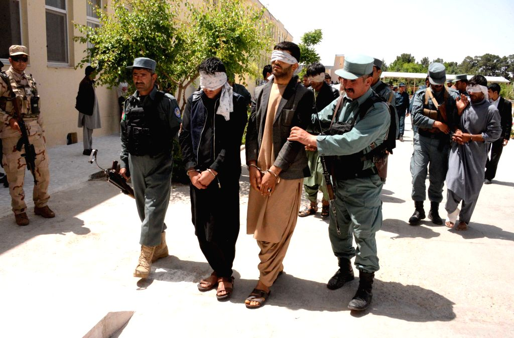 Afghan policemen escort captured terrorists in Herat province, Afghanistan, April 22, 2015. Afghan policemen captured nine terrorists with their ammunitions during ...