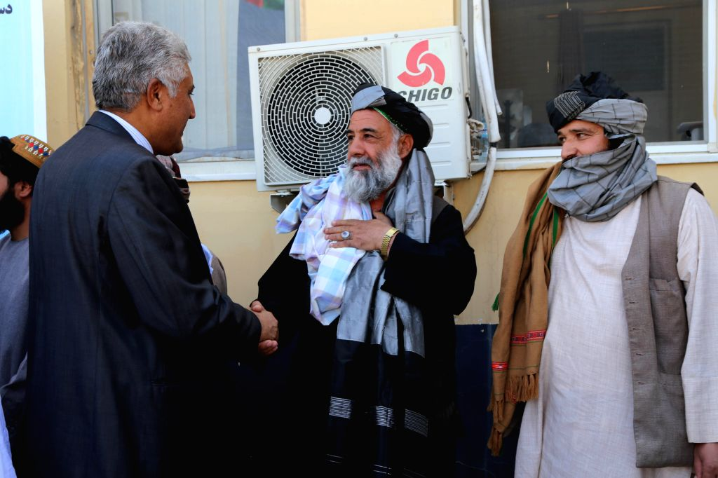 HERAT, Aug. 4, 2016 - A Taliban fighter shakes hands with a local official during a surrender ceremony in Herat province, Afghanistan, Aug. 3, 2016. Some 13 Taliban fighters gave up fighting in the ...
