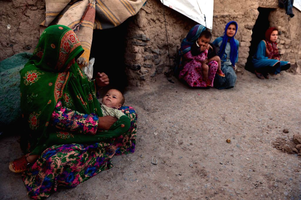 Afghan refugees sit outside their tents at a refugee camp in Herat province, west Afghanistan, May 18, 2015.