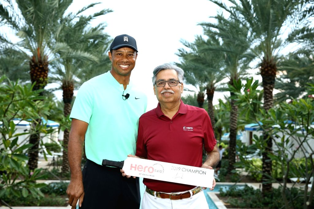 Hero MotoCorp Chairman Pawan Munjal hands over the trophy to golfer Tiger Woods - the 'Hero Shot 2019' winner - ahead of the Hero World Challenge 2019 in the Bahamas, on Dec 3, 2019.