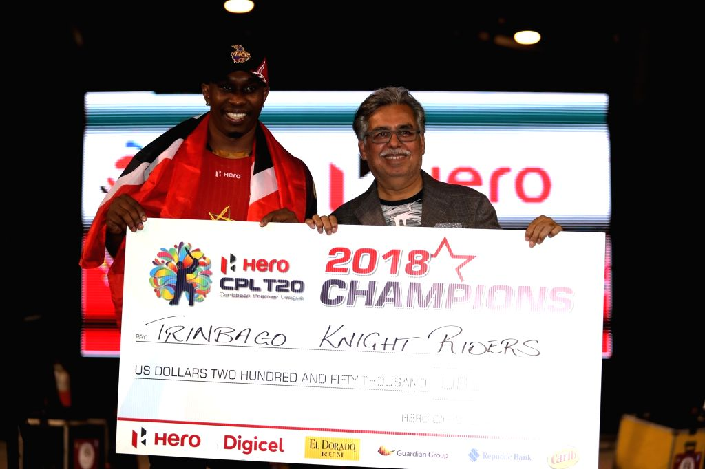 Hero MotoCorp CMD and CEO Pawan Munjal presents the Hero CPL T20 champions cheque to Trinbago Knight Riders captain Dwayne Bravo, in Gurugram, on Sept 17, 2018. - Dwayne Bravo