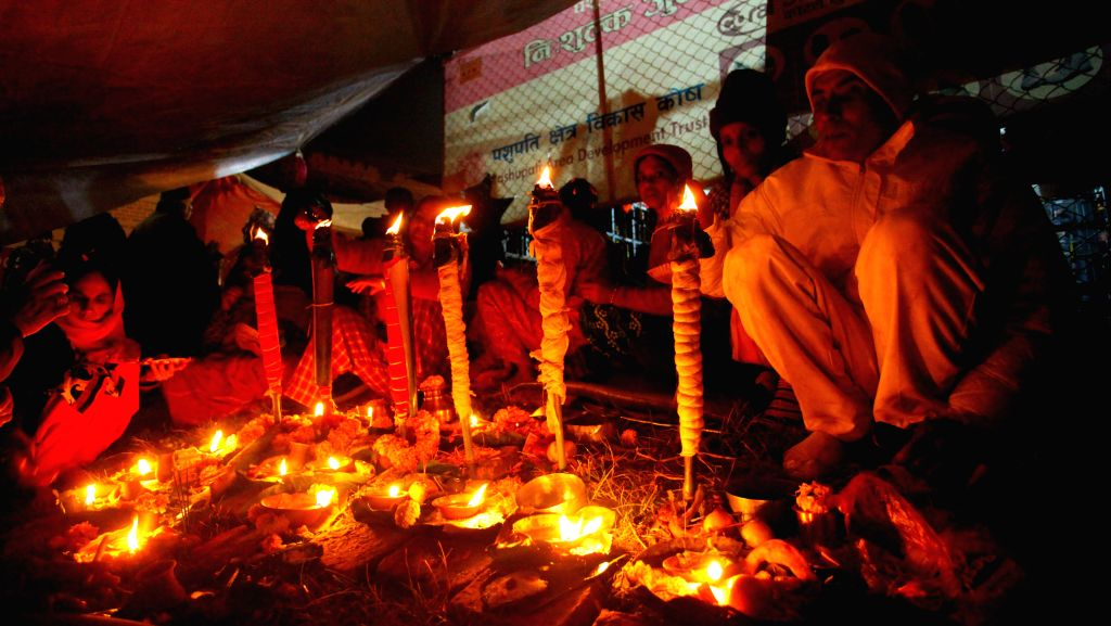 Hindu devotees light oil lamps to perform religious rituals during the Bala Chaturdashi Festival at the Pashupatinath Temple in Kathmandu, Nepal, Dec. 9, 2015. ...