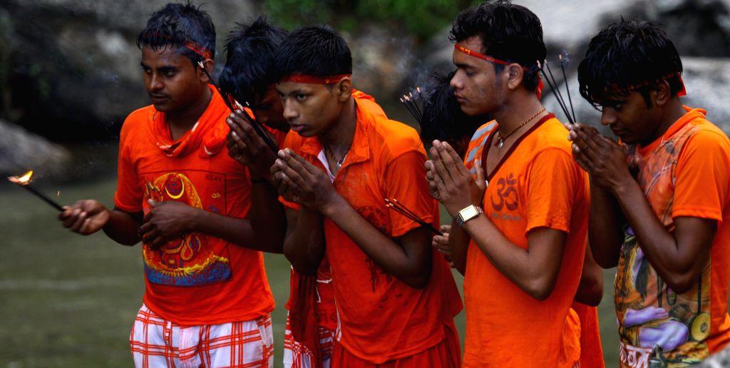 Hindu devotees offer prayers after collecting holy water from Bagmati river during the Bol Bom pilgrimage at Sudarijaal, Katmandu, Nepal, Aug. 10, 2015. During ...