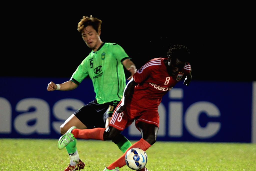 Moses Oloya (R) of Vietnam Becamex Binh Duong vies for the ball during the group stage of 2015 AFC Champions League against South Korea's Jeonbuk Hyundai ...