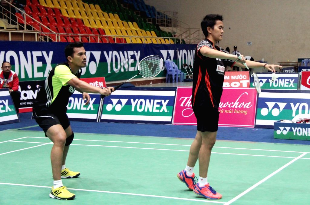Indonesian players Muhammad Rijal and Vita Marissa serve the ball during the Yonex Sunrise - Vietnam Open 2014 badminton tournament final match at Tan Binh
