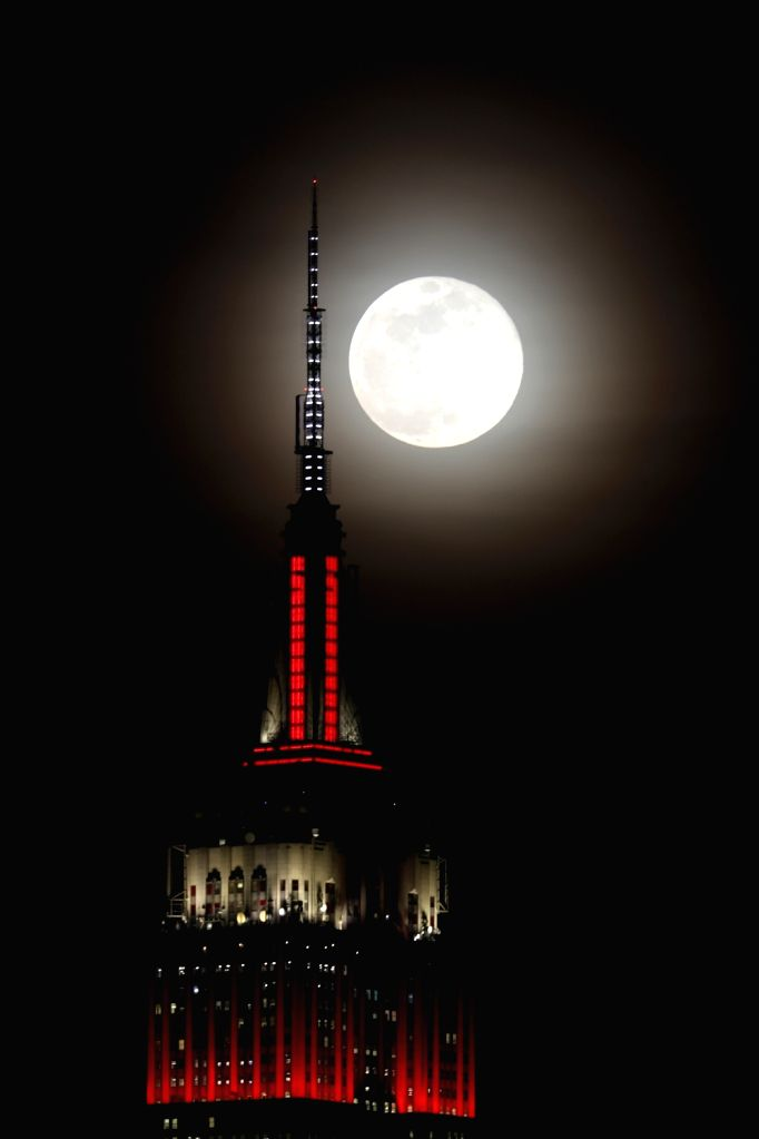 HOBOKEN (U.S.), Feb. 20, 2019 Photo taken from Hoboken of New Jersey shows a full moon rising up behind the Empire State Building in New York, the United States, on Feb. 19, 2019.