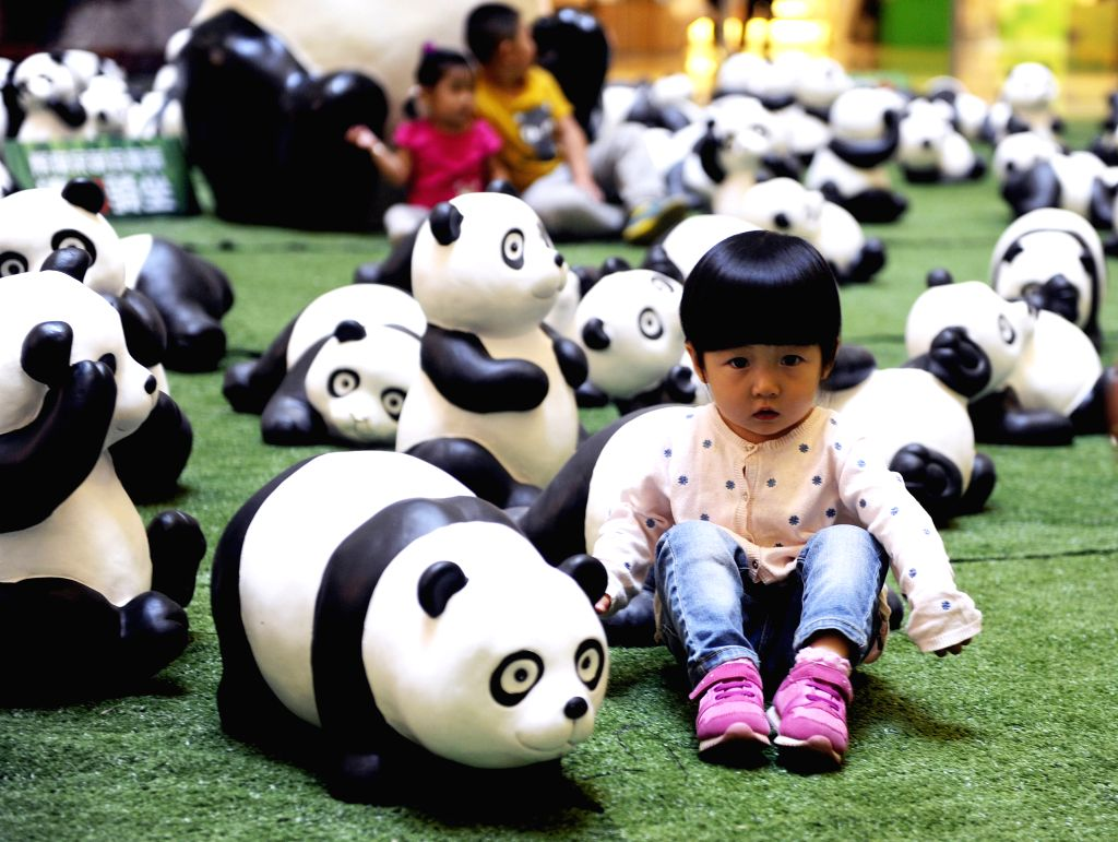 A child poses for photo with panda figures at a shopping mall in Hohhot, capital of Inner Mongolia Autonomous Region, Aug. 26, 2014. About 100 panda figures were ...