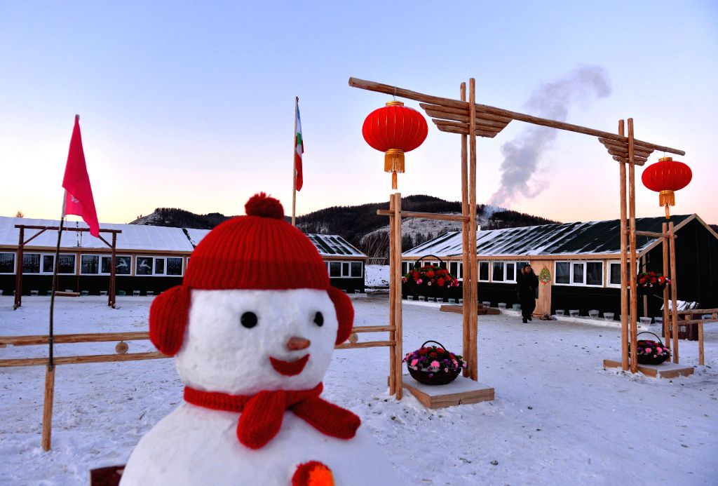 A snowman is seen in front of houses built for timberjacks the Moridaga Forestry Bureau in Dahinggan Mountain forest region in north China's Inner Mongolia ...