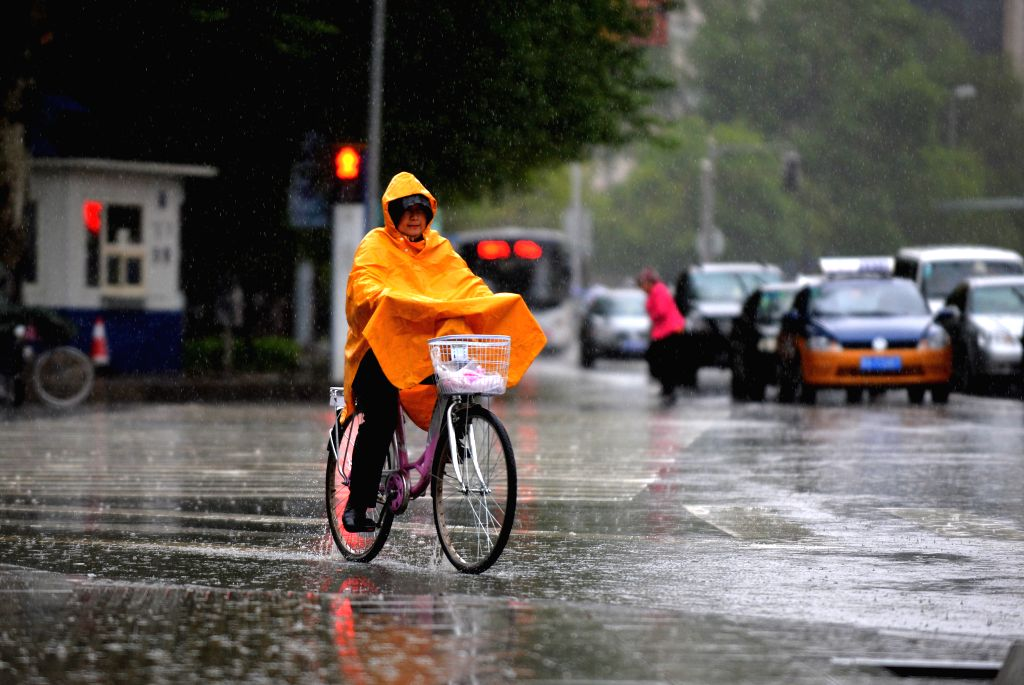 A citizen rides bicycle in rain in Hohhot, capital of north China's Inner Mongolia Autonomous Region, May 9, 2014. A rainfall hit Hohhot on Thursday night and Friday.