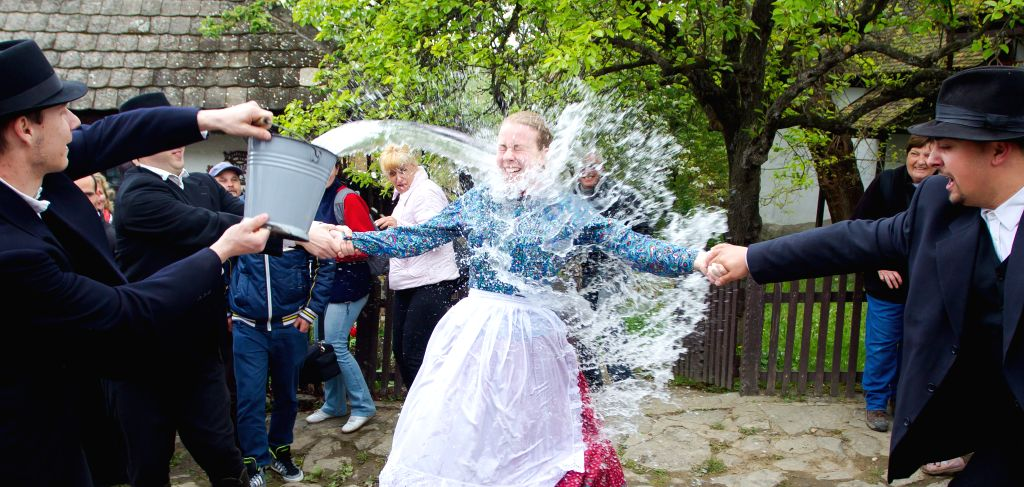 Local men splash water at a girl as part of traditional Easter celebrations in Holloko, a village in northern Hungary, April 21, 2014. Local people from Holloko, ..