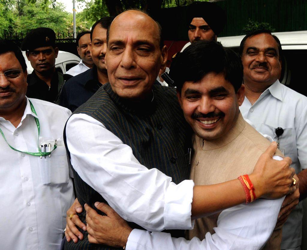 Home Minister Rajnath Singh greets BJP senior leader Shahnawaz Hussain on the occasion of Eid al-Fitr in New Delhi on July 29, 2014. - Rajnath Singh