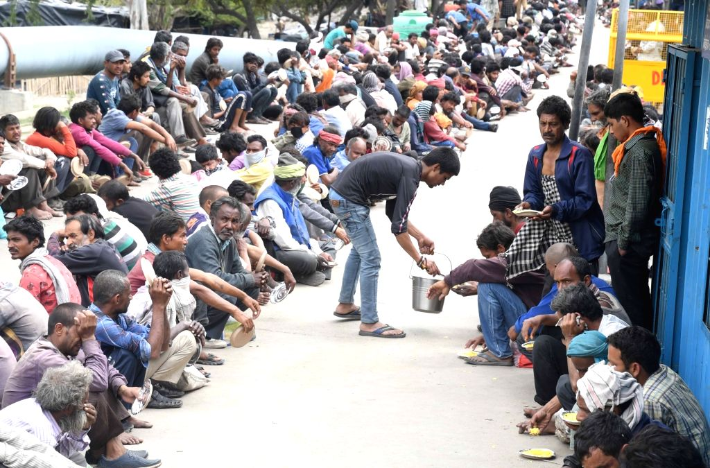 Homeless people and daily wagers receive food at a government shelter amid the nationwide lockdown, on Day 2 of the 21-day nationwide lockdown imposed by the Narendra Modi government over ... - Narendra Modi