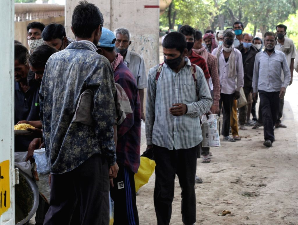 Homeless people stand in a que for food during the Curfew day at Kashmiri gate in New Delhi on Saturday, 17th April, 2021.