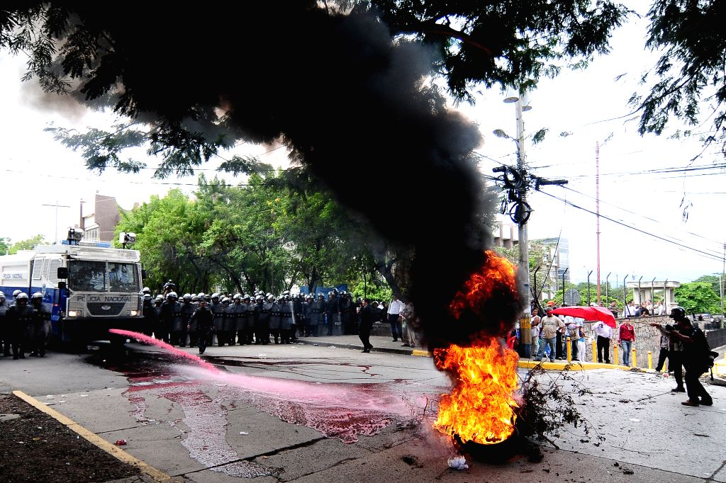Honduran police remove burning tires placed during a protest supporting Honduran journalist, David Romero, near Tegucigalpa Courts, in Tegucigalpa, Honduras, on ...