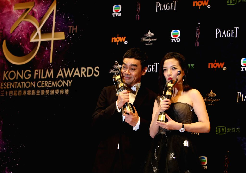 Actor Lau Ching Wan (L) holds the best actor award and actress Zhao Wei holds the best actress award as they pose at the 34th Hong Kong Film Awards in Hong Kong, ... - Lau Ching Wan