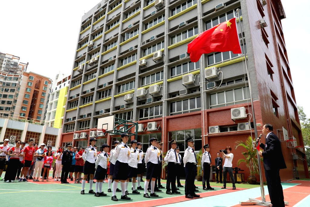 HONG KONG, Aug. 12, 2019 - People attend a flag raising ceremony at a middle school in Yuen Long of New Territories, Hong Kong, south China, Aug. 11, 2019. The Association of Hong Kong Flag-guards ...