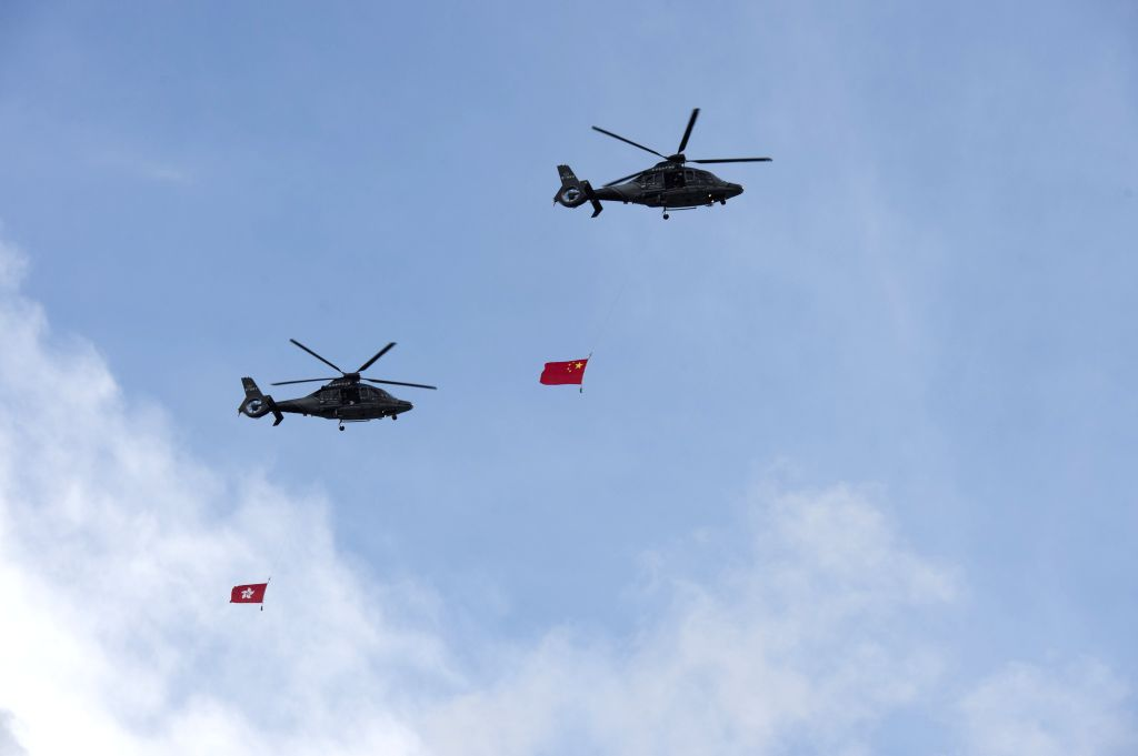 HONG KONG, July 1, 2016 - Helicopters carrying the Chinese national flag (R) and the flag of Hong Kong Special Administrative Region (HKSAR) fly over the Golden Bauhinia Square during a flag raising ...
