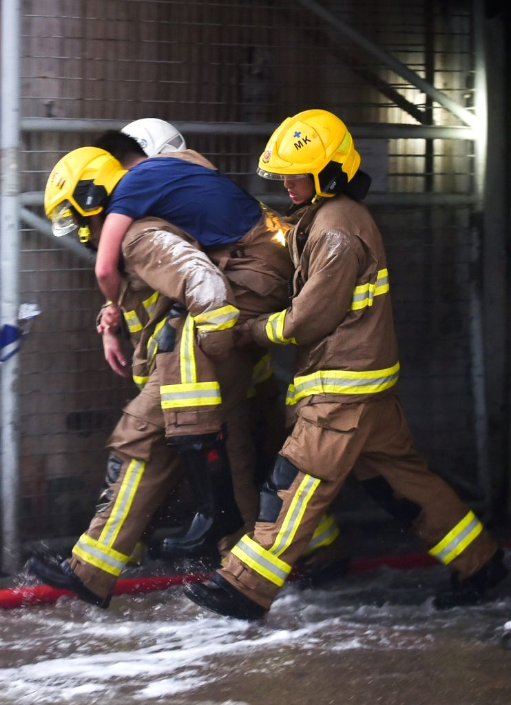 HONG KONG, Jun. 24, 2016 - Firefighters carry out an injured fellow at a burning multi-storey industrial building in East Kowloon area of Hong Kong, south China, June 23, 2016. A second firefighter ...