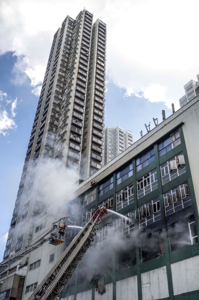 HONG KONG, June 23, 2016 - Firefighters work to put out fire at a multi-storey industrial building in East Kowloon area of Hong Kong, south China, June 23, 2016. The fire that broke out in an ...