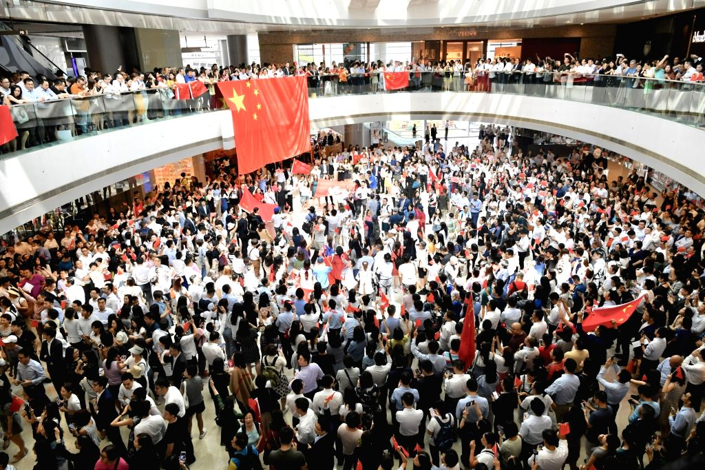 HONG KONG, Sept. 12, 2019 - People attend a flash mob at International Finance Center in Hong Kong, south China, Sept. 12, 2019. Participants chorused the Chinese national anthem during the flash mob ...