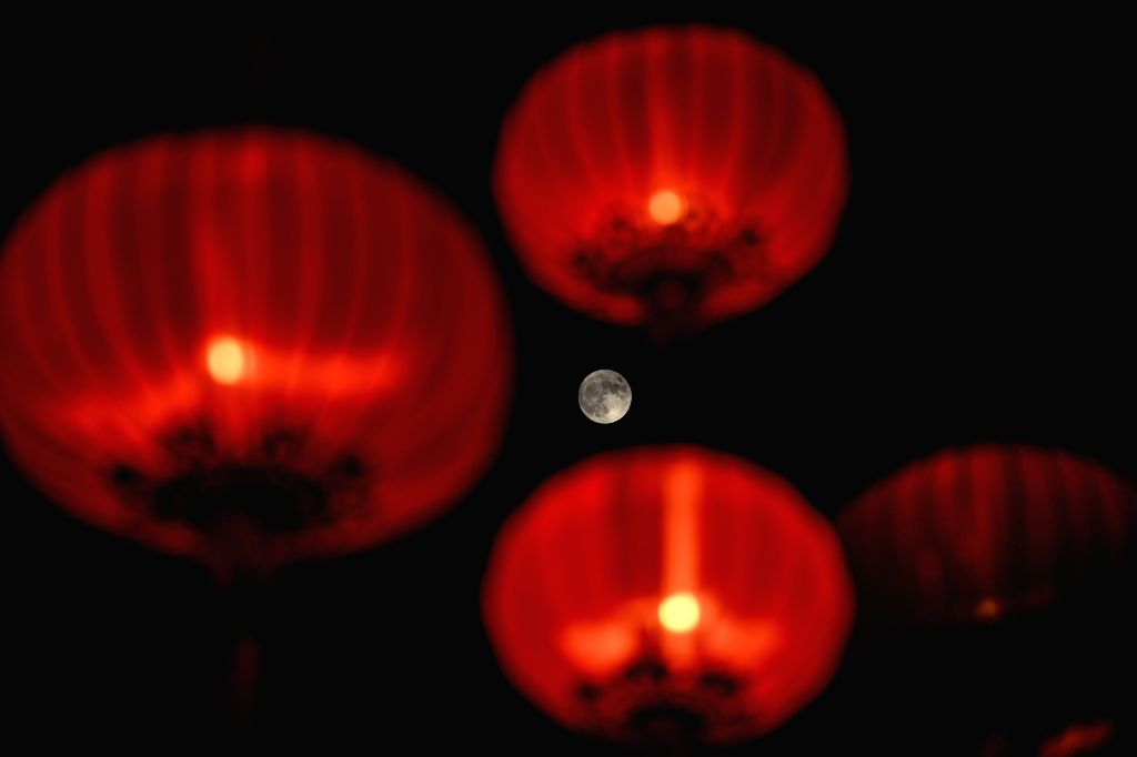 HONG KONG, Sept. 13, 2019 - A full moon is photographed during a lantern fair celebrating the Mid-Autumn Festival at Victoria Park in Hong Kong, south China, Sept. 13, 2019.
