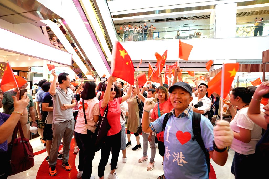 HONG KONG, Sept. 14, 2019 - Residents gather at the Amoy Plaza in Kowloon, who sing China's national anthem to show their support to a teacher beaten by protesters for singing that song days ago, in ...