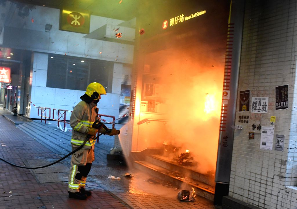 HONG KONG, Sept. 15, 2019 - A firefighter tries to put out a fire at the mass transit railway (MTR) Wan Chai station in Hong Kong, south China, Sept. 15, 2019. Rioters set fires in Central and ...