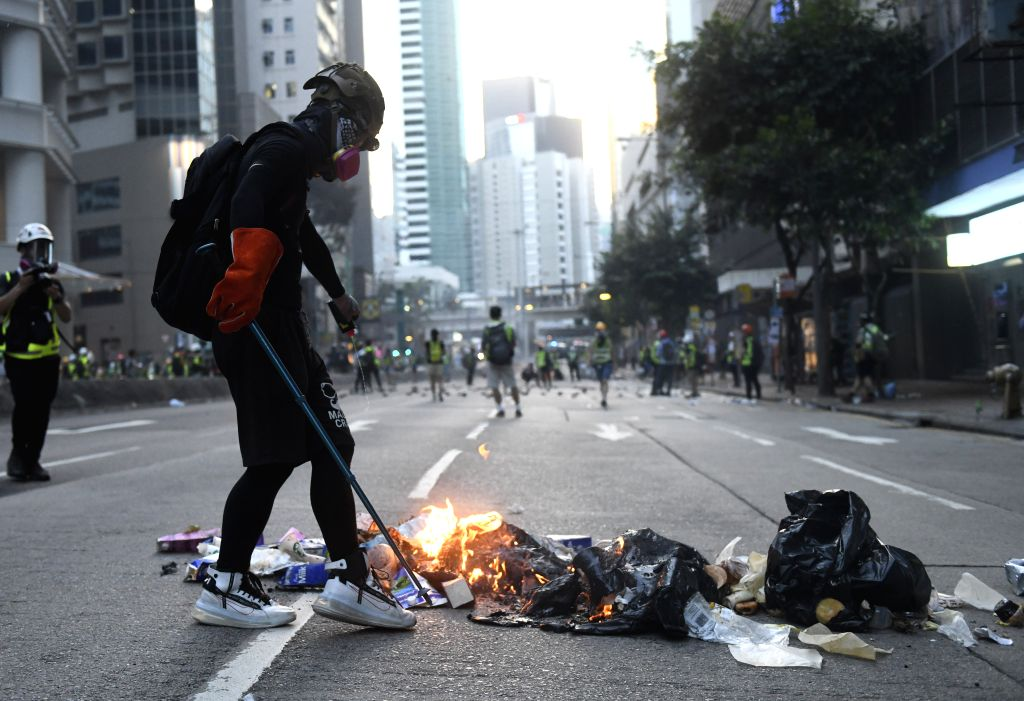 HONG KONG, Sept. 15, 2019 - A rioter sets a fire on Hennessy Road in Hong Kong, south China, Sept. 15, 2019. Rioters set fires in Central and Admiralty areas, threw petrol bombs at the Hong Kong ...