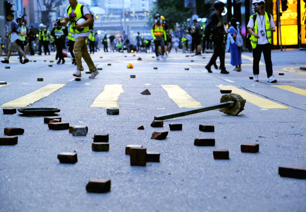 HONG KONG, Sept. 15, 2019 - Rioters throw bricks on the road in Wan Chai of Hong Kong, south China, Sept. 15, 2019. Rioters set fires in Central and Admiralty areas, threw petrol bombs at the Hong ...