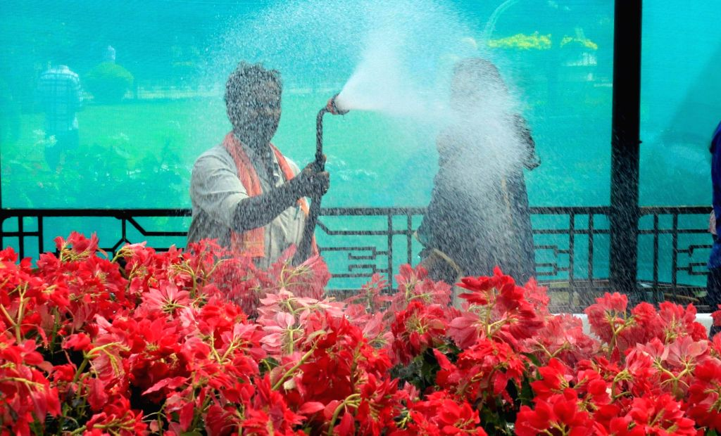 Horticulture staff sprinkling water to the flowers at the inauguration of the annual Republic Day National Flower Festival 2016 at Lalbagh, in Bengaluru, on Jan 16, 2016.