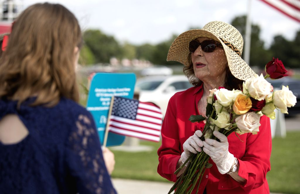 HOUSTON, May 27, 2019 - A volunteer hands out roses at the Houston National Cemetery on Memorial Day in Houston, Texas, the United States, on May 27, 2019. Hundreds of people attended the annual ...