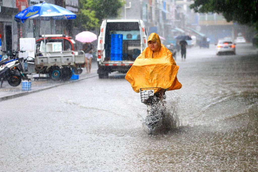 HUAI'A citizen rides on a waterlogged street following heavy rain in Huai'an City of east China's Jiangsu Province, July 5, 2018. The National Meteorological Center of ...