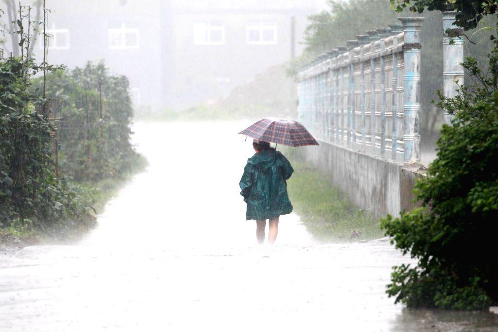 HUAI'A pedestrian wades through a waterlogged street following heavy rain in Huai'an City of east China's Jiangsu Province, July 5, 2018. The National Meteorological ...