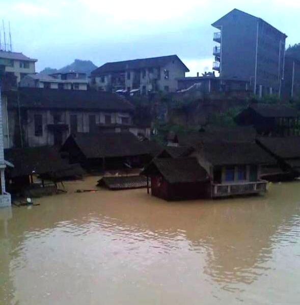 Photo taken with a mobile phone shows flooded houses in Mibei Township of Huaihua City, central China's Hunan Province, July 5, 2014. Rain-triggered landslides ...