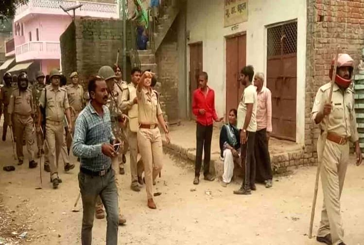Husband attacked his wife with an ax and later killed her by beating her with sticks by a mob in front of the Uttar Pradesh police.
