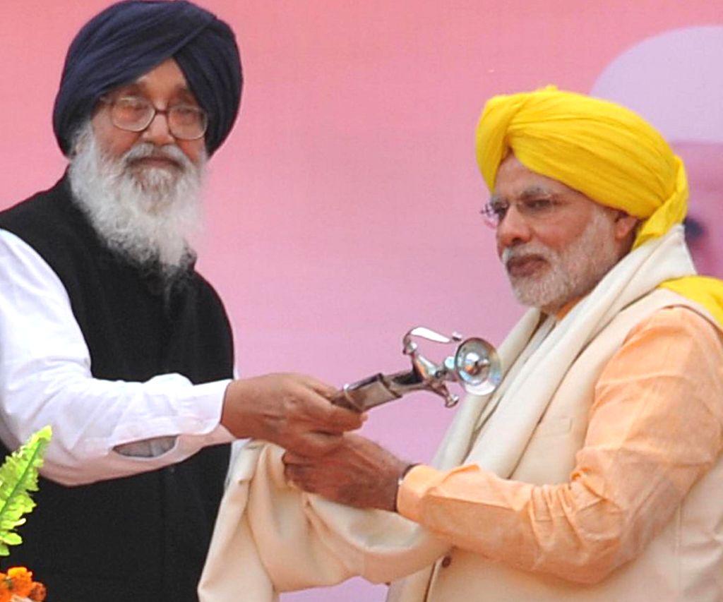Prime Minister Narendra Modi being honoured by Punjab Chief Minister Parkash Singh Badal at National Martyrs Memorial in Hussainiwala of Punjab's Firozpur on March 23, 2015. - Narendra Modi and Parkash Singh Badal