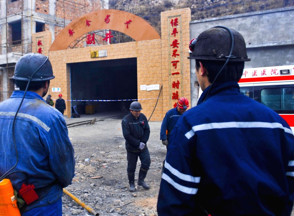 Miners wait at the entrance after a gas explosion occurred at the Baiyanggou coal mine in Hutubi County in the Hui Autonomous Prefecture of Changji, northwest ..