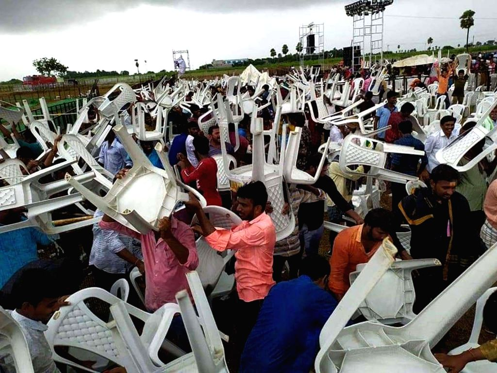 Huzur Nagar: Chairs being removed from the venue of Telangana Chief Minister K. Chandrashekar Rao's public meeting that was cancelled due to heavy rains and thunderstorm, in Huzur Nagar on Oct 17, ... - K. Chandrashekar Rao