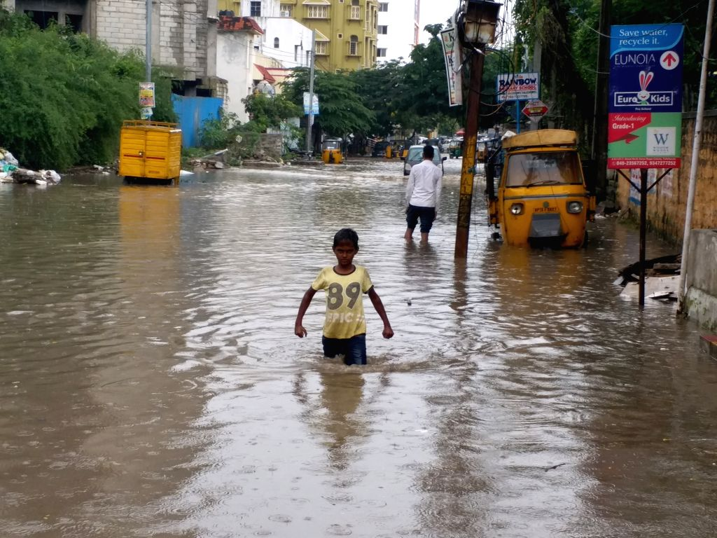 Hyderabad: A child struggles through a water-logged street after rains lashed Hyderabad on Oct 22, 2019. (Photo: IANS)