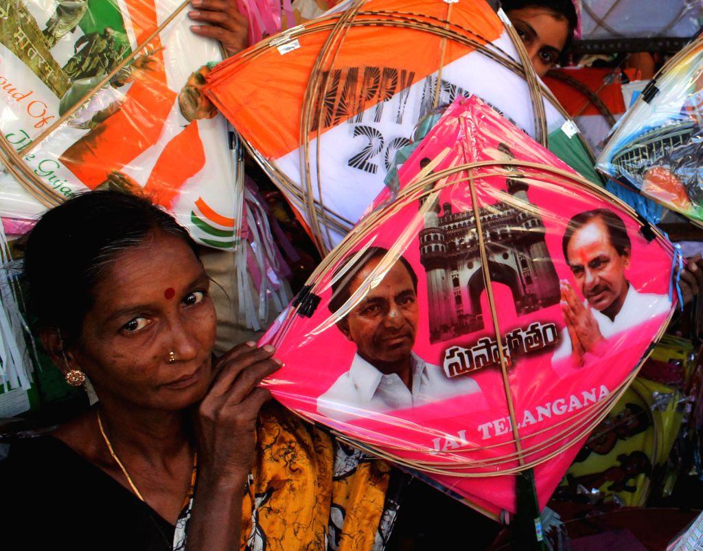 A lady holds a kite with a photo of Telangana Chief Minister K Chandrasekhar Rao at a shop ahead of Makar Sankranti festival in Hyderabad, on Jan 10, 2015. - K Chandrasekhar Rao
