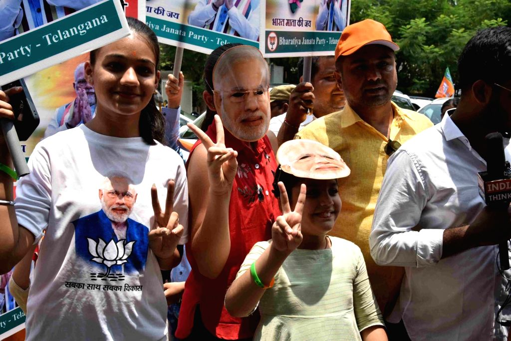 Hyderabad: BJP supporters celebrate after the party led by Prime Minister Narendra Modi appeared set to retain power as its candidates alone led in 294 of the 541 Lok Sabha seats with its allies faring equally well across the country, in Hyderabad on - Narendra Modi