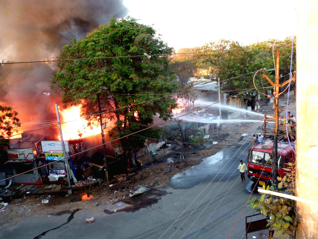 Firefighters try hard to douse a fire that broke out in a a gas cylinder godown in Hyderabad, on March 15, 2015.