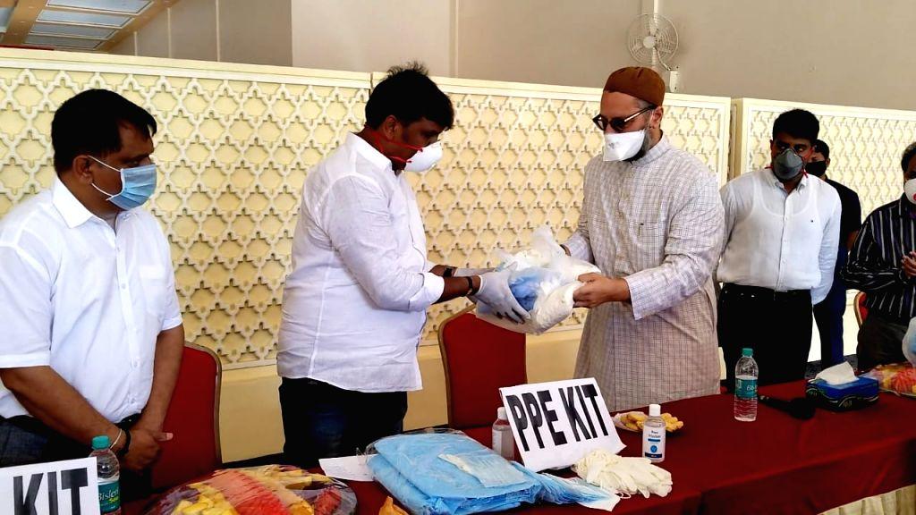 Hyderabad MP Asaduddin Owaisi handing over PPE kits to Greater Hyderabad Mayor Bonthu Rammohan.