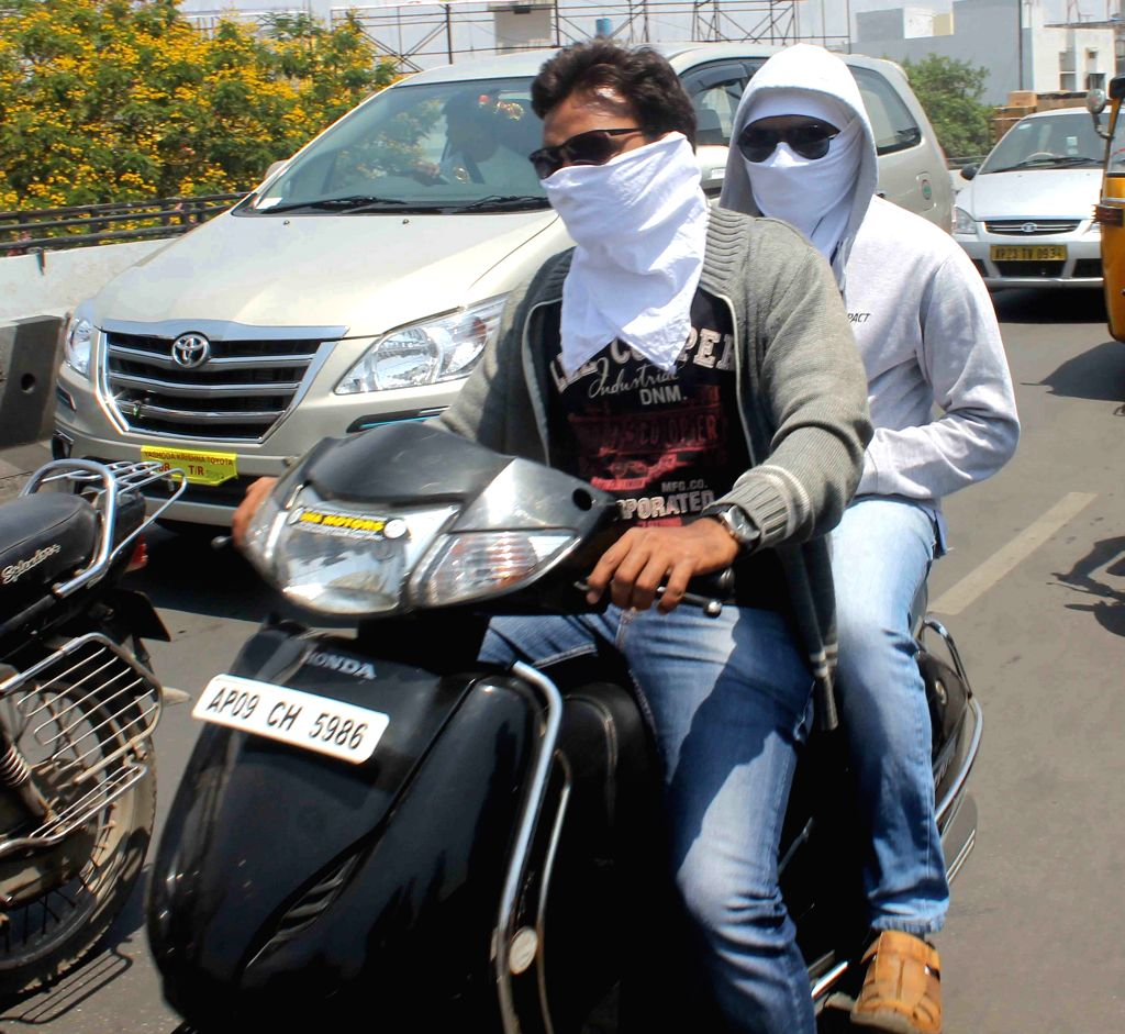 People cover their face to protect themself from the heat wave in Hyderabad, on April 4, 2015.
