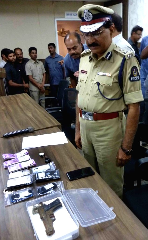 Hyderabad Police Commissioner Mahender Reddy presents stolen cash and mobile phones before media recovered from the youths arrested in the Vikram Goud firing case in Hyderabad on Aug 2, ...