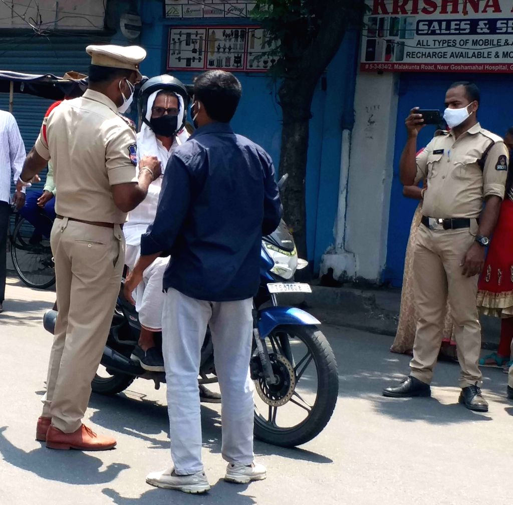 Hyderabad :  Police personnel checking and seized vehicle of  Girls and women's going to marriage party during the lockdown imposed to curb at Gousha mahal Circle  on Sunday  in Hyderabad 23 May 2021.  (Photo: IANS)