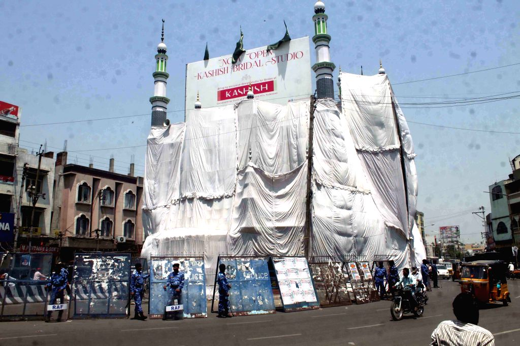 Police stand guard in front of a mosque during Hanuman Jayanti `Shobha Yatra` in Tadbun at Hyderabad, on April 4, 2015.