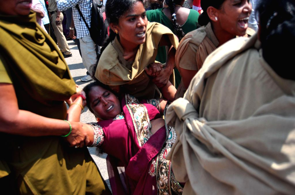 Policewomen take away Anganwadi workers who were staging a demonstration to press for their demands in in Hyderabad on March 17, 2015.