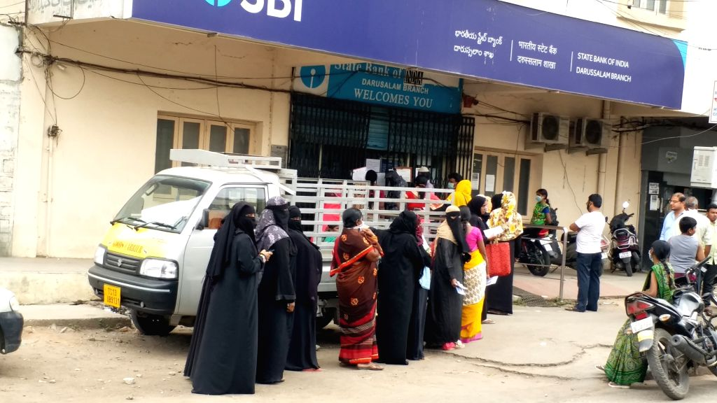 Hyderabad: Women not practising social distancing as they queue up outside a SBI Bank during the 21-day nationwide lockdown imposed as a precautionary measure to contain the spread of coronavirus, in Hyderabad on April 4, 2020. (Photo: IANS)