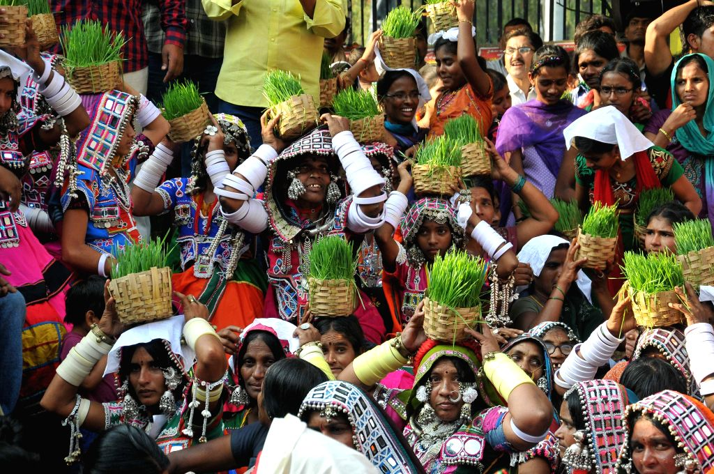 Women with sapling pots on their head participate in Telangana Girijana Festival in Hyderabad on Dec 14, 2014.